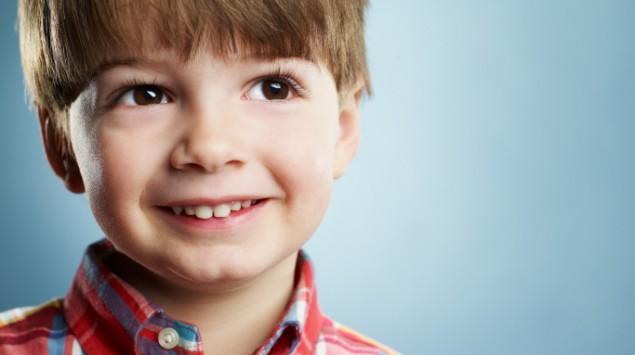 Lächelnder kleiner Junge mit brauen Haaren und Augen.