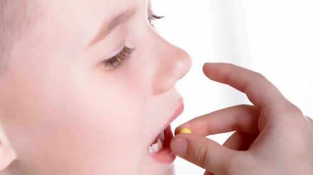 Junge steckt sich eine Tablette in den Mund.