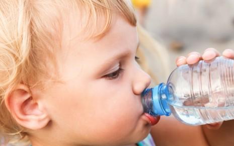 Ein Junge trinkt aus einem Glas.