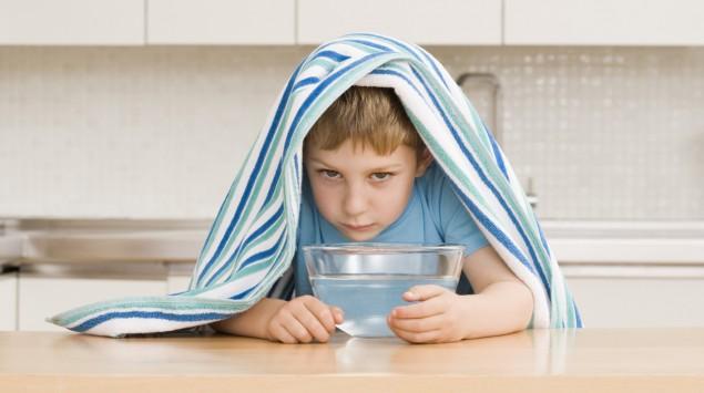 Junge inhaliert über Wasserbad.