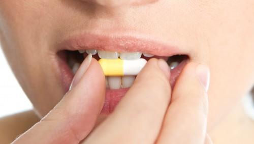 Eine Frau ist im Begriff, eine Kapsel (Arzneimittel) zu schlucken.