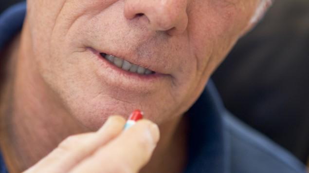 Ein älterer Mann nimmt eine Tablettenkapsel ein.