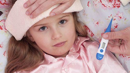 Mädchen liegt mit Fieber im Bett.