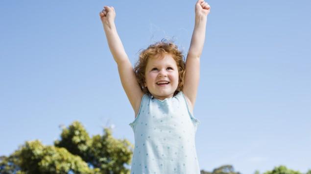 Ein Kind streckt die Hände in die Luft.
