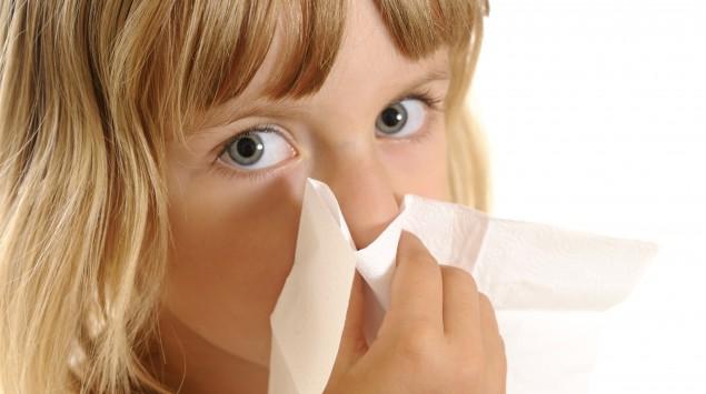 Ein kleines Mädchen putzt sich die Nase.
