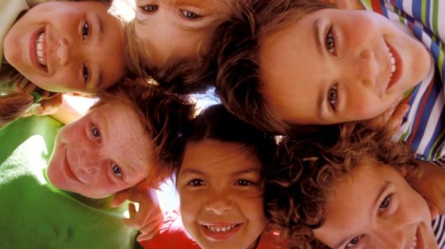 Gruppe Kinder steckt die Köpfe zusammen.