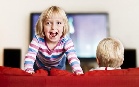 ADHS-Kind tobt auf der Couch vor dem Fernseher