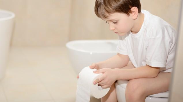 Ein Junge sitzt auf der Toilette