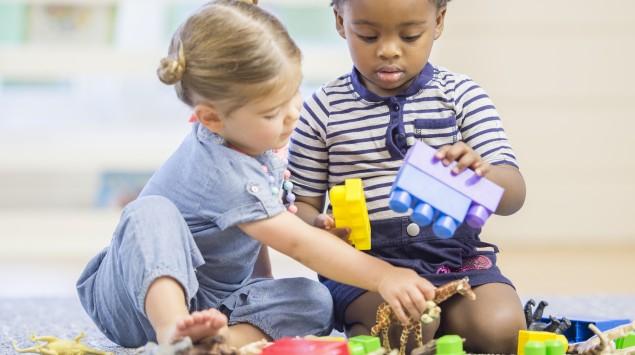 Kinder spielen im Kindergarten mit Bauklötzen.