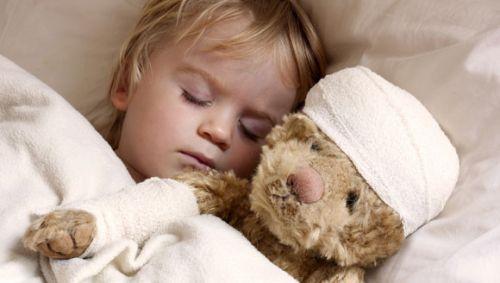 Das Bild zeigt ein krankes Kind im Bett mit einem Teddybären.