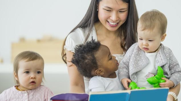 Eine Frau spielt mit drei Kindern.