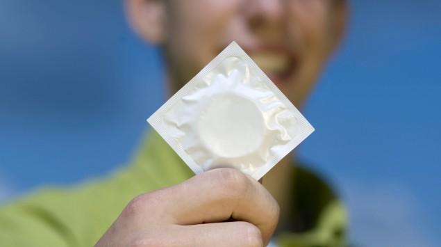 Ein junger Mann hält eine Kondompackung in die Luft.