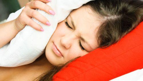 Eine Frau liegt im Bett und hält sich mit einem Kopfkissen das Ohr zu.