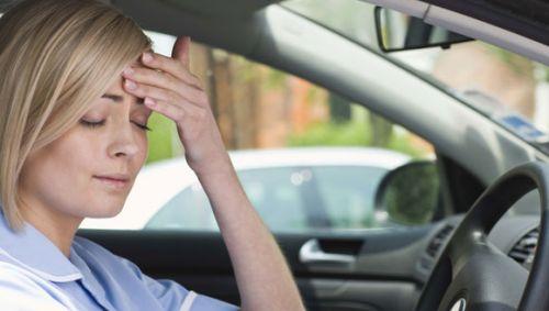 Das Bild zeigt eine Frau im Auto, die sich an den Kopf fasst.