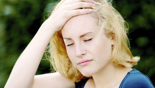 Eine blonde Frau fasst sich an den Kopf.