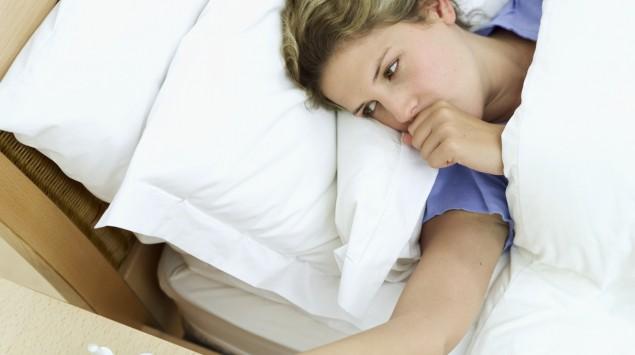 Frau liegt im Bett und hustet.