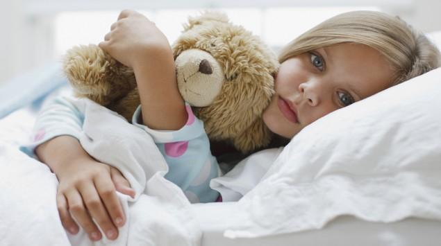 Ein krankes Mädchen liegt im Bett.