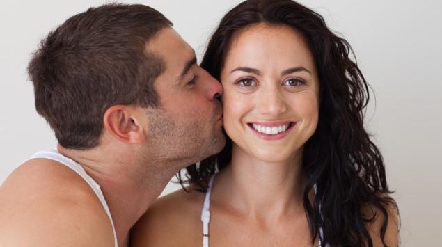 Ein Mann küsst seine Freundin auf die Wange.