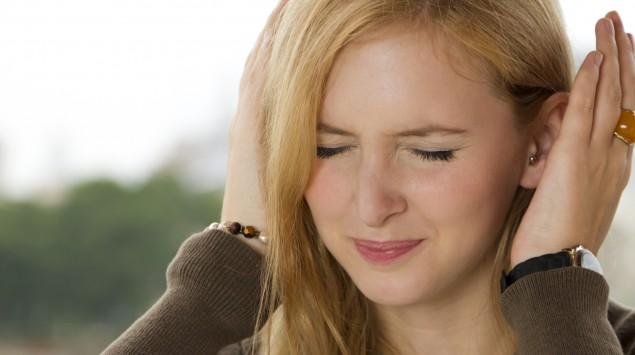Eine blonde Frau hält sich die Ohren zu.