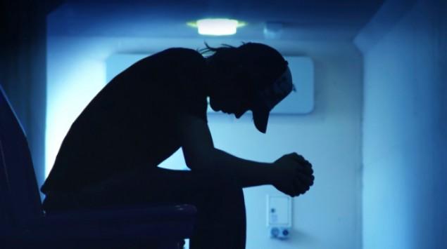 Der Umriss einer Person, die mit gesenktem Kopf im Dunkeln sitzt.