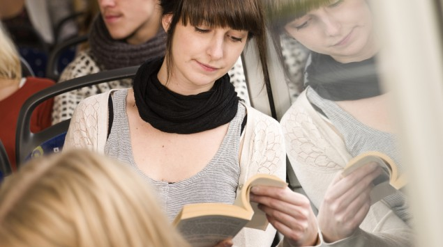 Eine junge Frau liest im Bus ein Buch.