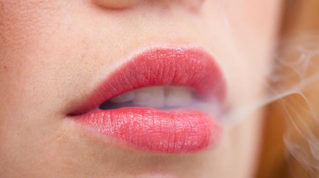 Zwischen den Lippen einer Frau entweicht Zigarettenrauch.