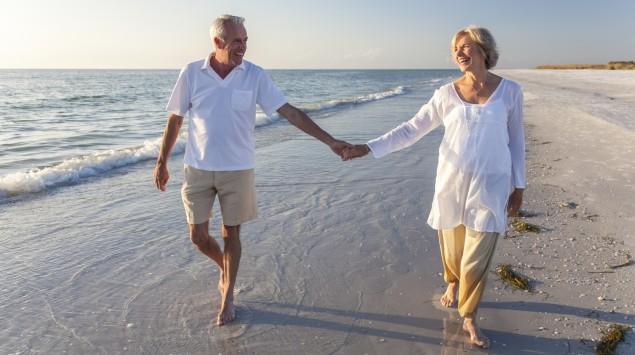 Ein älteres Paar geht am Strand spazieren.