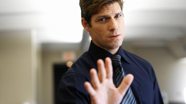Ein Mann hebt abwehrend die Hand.