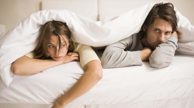 Das Bild zeigt ein frustriertes Paar im Bett.