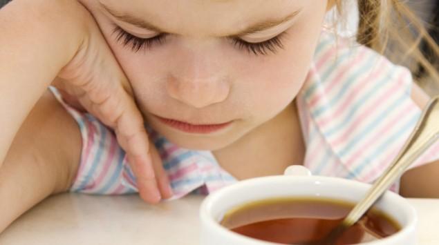 Ein Mädchen sitzt ablehnend am Tisch, vor ihr eine Tasse Tee.