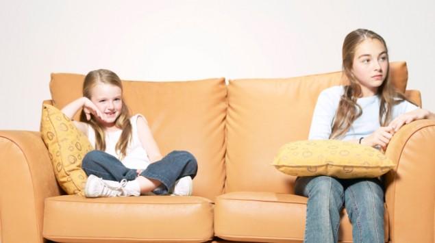 Zwei Mädchen sitzen voneinander abgerückt auf der Couch.