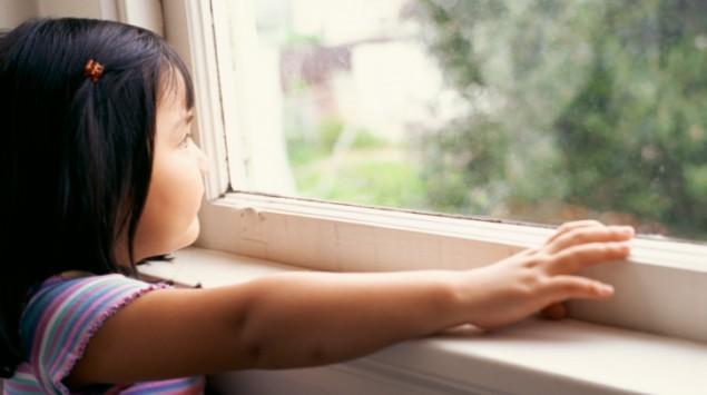 Kleines Mädchen schaut traurig aus dem Fenster.
