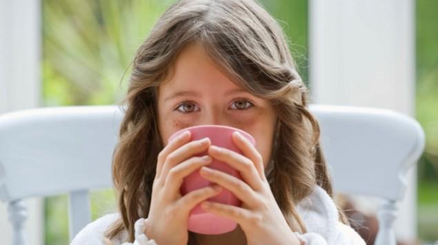 Mädchen hält eine Tasse in der Hand.