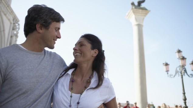 Ein Pärchen hält sich im Arm, im Hintergrund sieht man die Säulen des Markusplatzes (Venedig).
