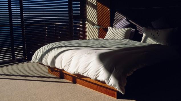 Das Bild zeigt ein Bett in einem abgedunkelten Schlafzimmer.