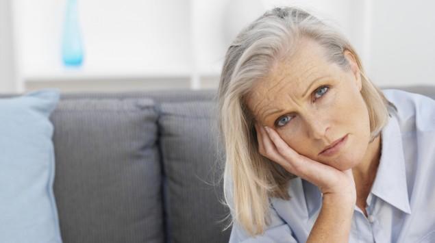 Das Bild zeigt eine ältere Frau, die müde und erschöpft aussieht.