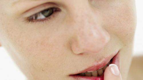 Eine Frau fasst sich mit dem Finger an die Lippen.