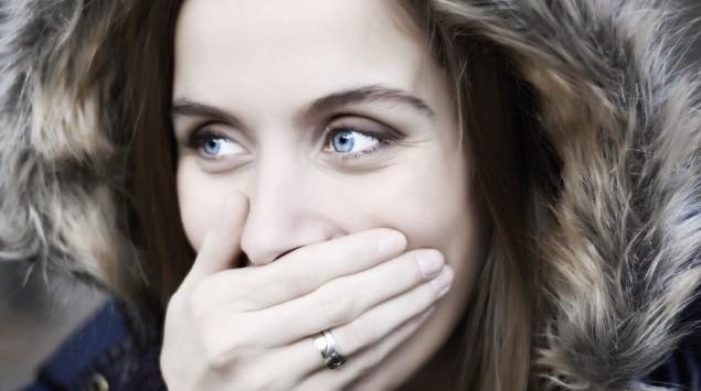 Man sieht eine Frau mit einer Fellkapuze, die sich die Hand vor den Mund hält.