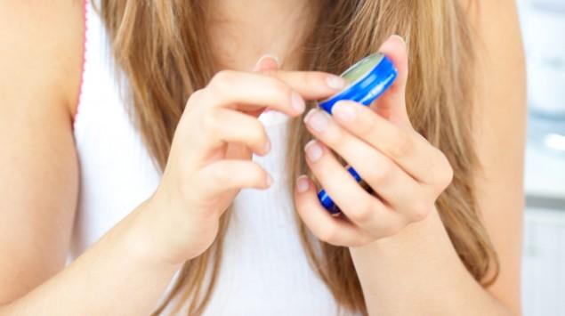 Ein Mädchen hält eine Dose mit Salbe in den Händen.