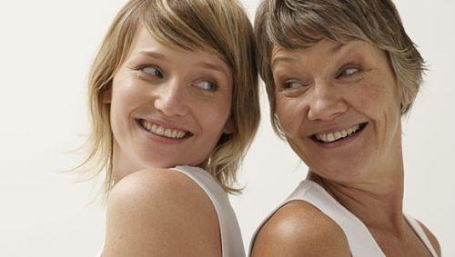 Mutter und Tochter stehen Rücken an Rücken und lachen sich an.