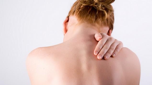 Die Rückansicht einer Frau, die sich an den Nacken fasst.