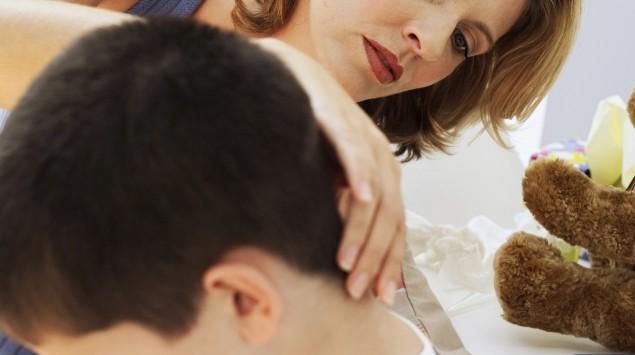 Eine Frau untersucht den Nacken eines Jungen.