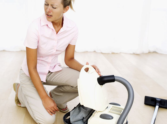 Das Bild zeigt eine Frau, die einen Staubsauger öffnet und niest.