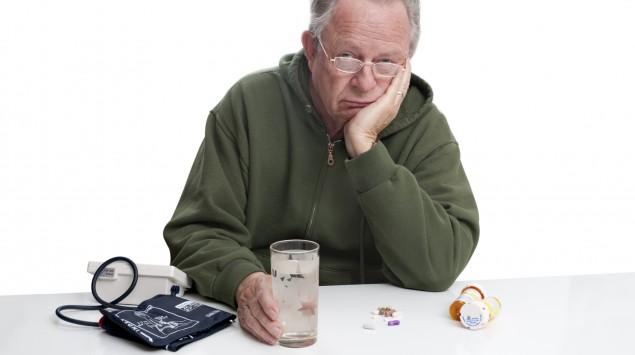 Ein Mann sitzt niedergeschlagen vor seinem Blutdruckgerät.