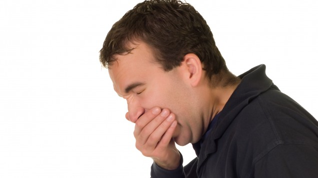 Ein Mann niest in die Hand.