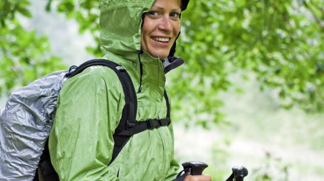 Eine Frau beim Nordic Walking im Wald, sie trägt Regenkleidung.
