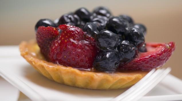 Das Bild zeigt ein Stück Obstkuchen mit Heidelbeeren und Erdbeeren.