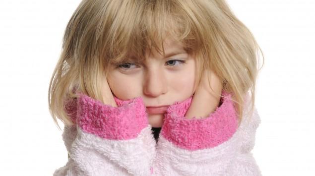 Ein kleines Mädchen hält sich die schmerzenden Ohren.
