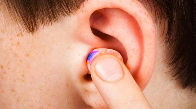 Das Bild zeigt ein Ohr mit Ohrenstöpsel.