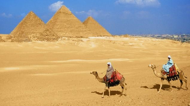 Man sieht Pyramiden und Männer auf Kamelen.